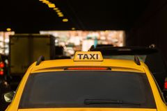 Yellow taxi moves in the midst of cars along city streets. Yellow taxi moves in the midst of cars along city streets at night. Back view Royalty Free Stock Image