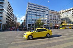 Yellow taxi and people waiting to cross the road at Syntagma Athens Greece Royalty Free Stock Images