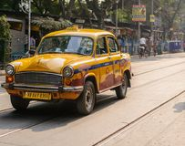 Yellow Taxi riding on street in Kolkata Stock Image