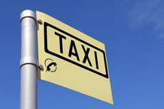 Yellow Taxi Sign against Blue Sky Stock Photography