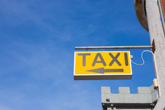 Yellow Taxi Sign against the blue sky. In the city Royalty Free Stock Photography