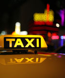 Yellow taxi sign on car roof. Close up of illuminated yellow taxi sign reflecting on taxicab roof, neon light in background, night scene Royalty Free Stock Photo