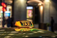 Yellow taxi sign on at night in a metropolis. Yellow taxi sign at night in a metropolis. Place for the inscription, the concept of a modern city, comfort Royalty Free Stock Photos