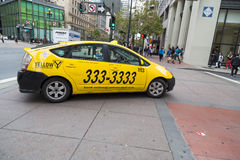 Yellow taxicab making turn on streets of San Francisco, California Stock Photo
