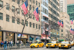Yellow taxicabs and american flags on the 5th Avenue - New York City Stock Photo
