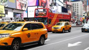 Yellow taxis and touristic bus in Times Square New York City. New York City, USA - April 2018: Yellow taxis and touristic bus in Times Square stock video