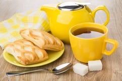 Yellow teapot, cup of tea, spoon, lumpy sugar, pies Stock Photos
