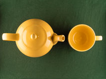 Yellow teapot and empty mug, copy space, top view. Yellow teapot and empty mug, simple minimal top view of kitchenware with copy space Stock Photos