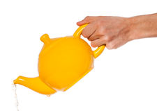 Yellow teapot in hand isolated Stock Images
