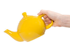 Yellow teapot isolated in hand on white background Royalty Free Stock Photo