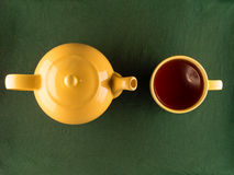 Yellow teapot and mug with tea, copy space. Yellow teapot and mug with tea, simple minimal top view of kitchenware with copy space Stock Photos