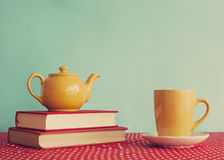 Yellow teapot over books Royalty Free Stock Images