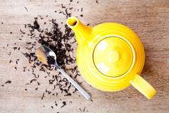 Yellow teapot with spoon and tea Royalty Free Stock Photography