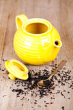 Yellow teapot with spoon and tea Royalty Free Stock Photo