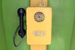 Yellow telephone. Old yellow telephone in green booth, Uzbekistan Royalty Free Stock Images