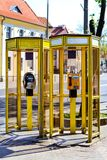 Yellow telephone booths with payphones. Bialystok. Yellow glass telephone booths with payphones are located on a pedestrian street. Obsolete means of telephone Royalty Free Stock Image