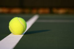 Yellow Tennis Ball On Court. Focus on yellow tennis ball.  White painted court line is also visible in image.   Background of image is in blur Stock Photos