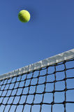 Yellow Tennis Ball Flying Over the Net. Against a Clear Blue Sky royalty free stock images