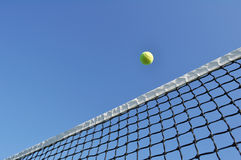 Yellow Tennis Ball Flying Over the Net. Against a Clear Blue Sky stock photos