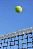 Yellow Tennis Ball Flying Over the Net. Against a Clear Blue Sky stock photo