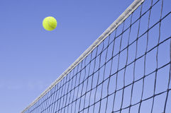 Yellow Tennis Ball Flying Over the Net Royalty Free Stock Image