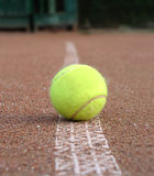 Yellow tennis ball lays on outdoor court marking line Stock Images