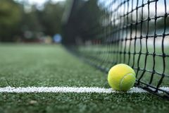 Yellow tennis ball at the net. On the court royalty free stock images