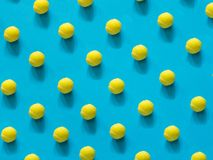 Yellow tennis ball patter on blue. Background stock photo