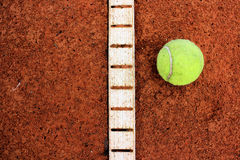 Tennis ball on red field Stock Image