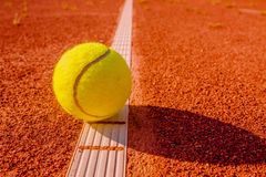 Yellow tennis ball touching the line Stock Photos
