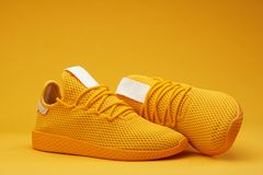 Yellow tennis shoes. Yellow tennis modern shoes isolated on orange background stock image
