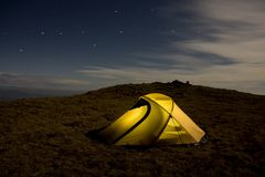 Yellow tent behind Ursa Major. A yellow tent in mountains, in the middle of the night behind Ursa Major Stock Photo