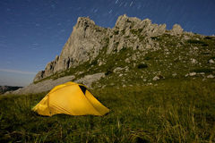 A yellow tent illuminated in mountains. In the middle of the night Stock Image