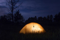 Yellow tent lighting at night in wildness.  Stock Photography
