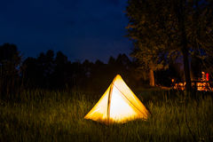 Yellow tent lighting at night in wildness.  Stock Photos