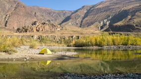 Yellow tent near mountain river. Yellow tent pitched near a river or stream in a mountain setting stock footage