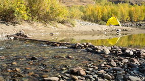 Yellow tent near mountain river. Yellow tent pitched near a river or stream in a mountain setting stock video footage