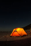 Yellow tent at night on the shore of lake Baikal in winter Stock Photo