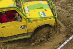 Yellow terrain vehicle exceeds a deep pool Royalty Free Stock Images