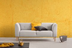Yellow texture on the wall and couch with pillows, real photo with copy space. Yellow texture on the wall of elegant living room with stylish couch with pillows royalty free stock photo