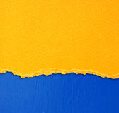 Yellow textured torn paper over blue wall background Royalty Free Stock Photo