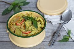 Yellow Thai curry in a bowl on wooden table stock photography