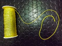 Yellow thread spool,on a black surface. Spool isolated object fiber rope reel roll string textile strong polyester repair thin skin sew yarn yellow  silk tailor Royalty Free Stock Images