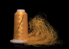 Yellow  threads and spool of thread with sewing needle Royalty Free Stock Image