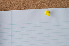 Yellow Thumb Tack Holding Paper on Cork Board Stock Photography
