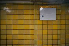 Yellow tile wall with blank board stock image