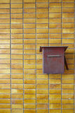 Yellow tiles wall with red rusty postbox. Background pattern Stock Photos