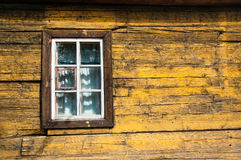 Yellow timbered wooden wall with white window. Yellow timbered wooden loghouse wall with window Stock Image