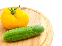 Yellow tomato and cucumber on cutting board Stock Image