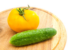 Yellow tomato and cucumber on wooden cutting board Stock Photography